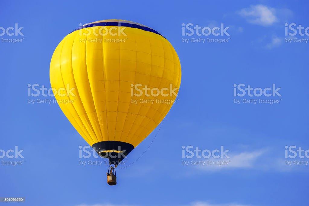 Yellow balloon in blue sky stock photo