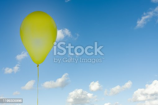 1141701990 istock photo Yellow balloon isolated at blue sky with clouds 1199305996