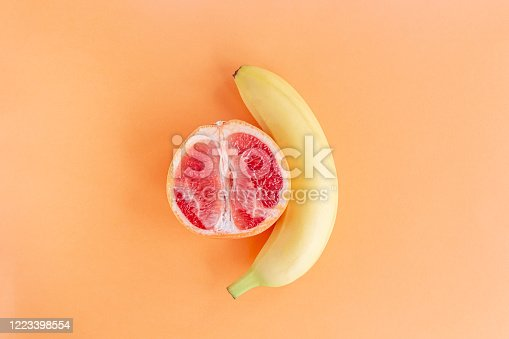istock Yellow banana and grapefruit on a pastel orange background, marital love concept 1223398554