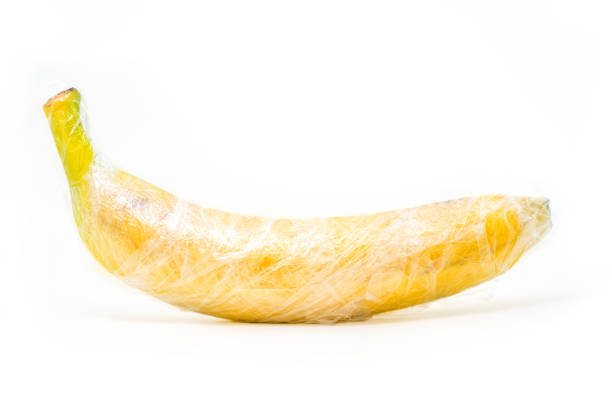 yellow banana is wrapped by plastic film,  protection concept stock photo