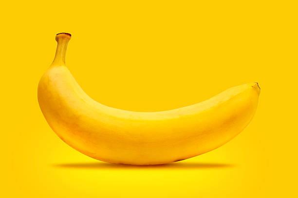 la banane jaune - fond couleur uni photos et images de collection