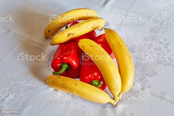 Yellow bananas and red pepper lie on a table