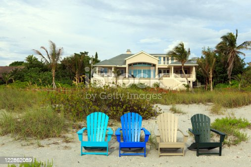Yellow beach house on Captiva Island, Florida, with four colored Adirondack Chairs on the sand, turquoise, blue, yellow and green.  There is dune grass and palm trees in the background and a partly cloudy sky.  The color image is in horizontal orientation with copy space for text.