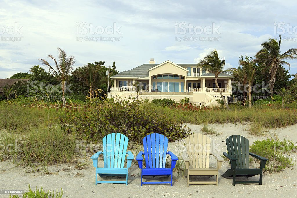 Yellow Beach house with colored chairs stock photo