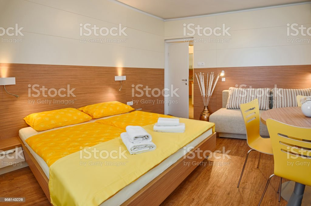Yellow bedroom with white towels on yellow bedding