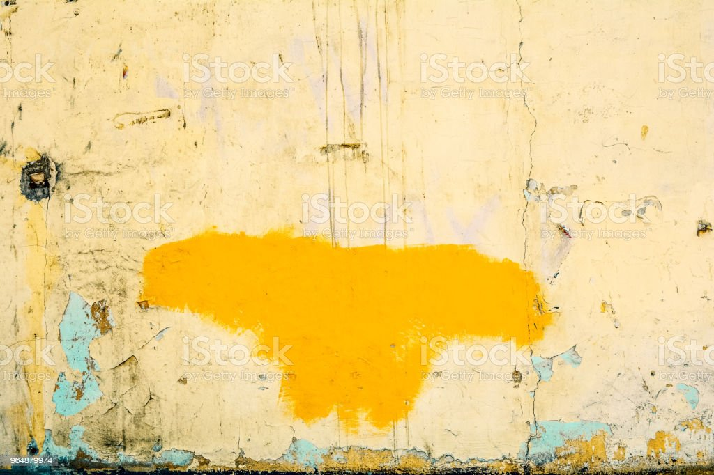 Yellow beige concrete wall with cracks, painted yellow butterfly shaped figure royalty-free stock photo