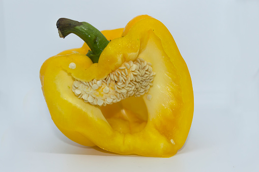 A cut yellow bell pepper with seeds inside in white background.