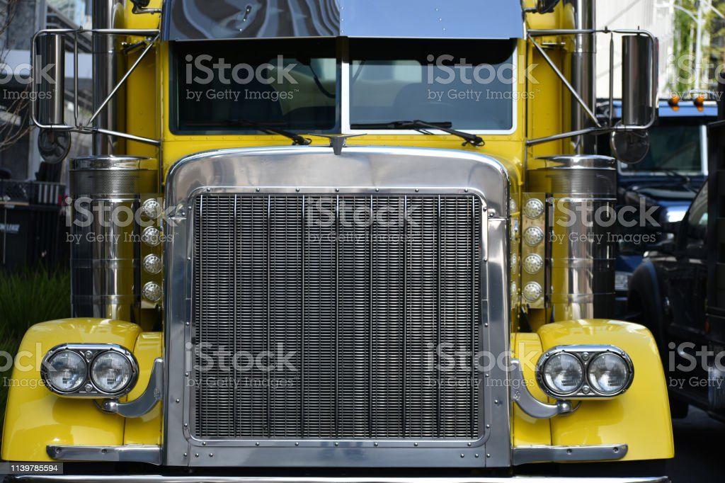 Yellow Big Rig Truck with Grill and Head Lights Close-up stock photo