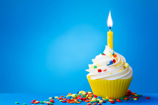 Yellow birthday cupcake stock photo