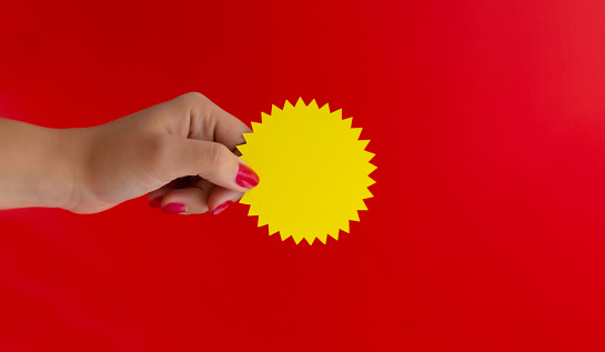 yellow blank sticker to demonstrate the discount in hand on a red background, layout with space for text and copy space. High quality photo