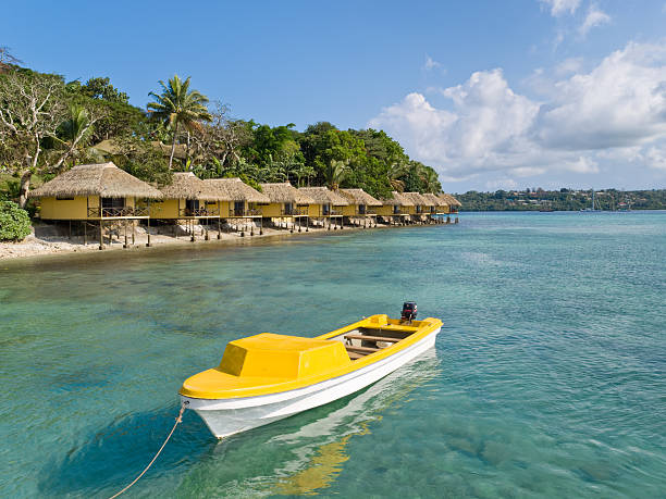Yellow Boat in Front of Iririki, Vanuatu Yellow Boat in Front of Iririki island in Vanuatu vanuatu stock pictures, royalty-free photos & images