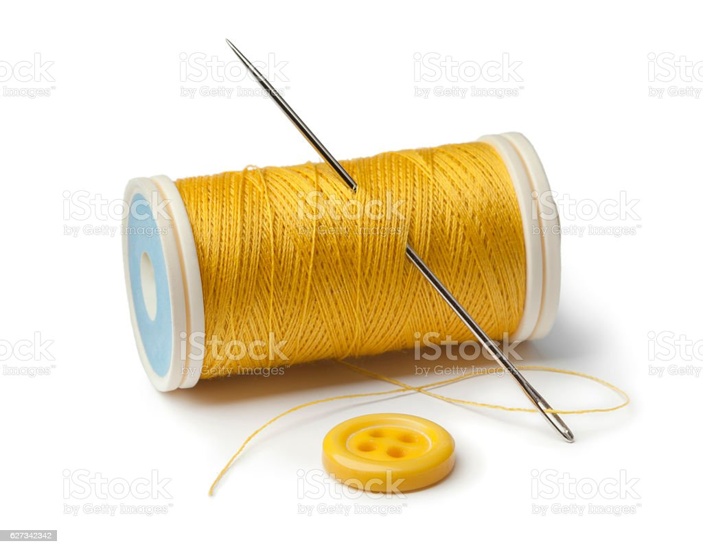 Yellow bobbin, needle and sewing button - foto de acervo