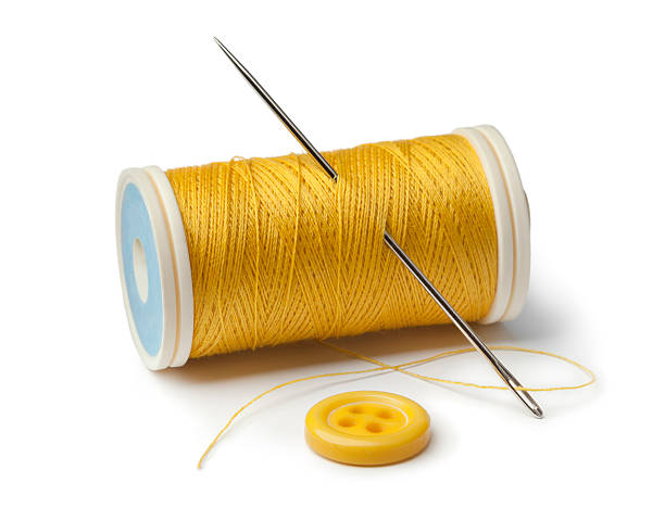 Yellow bobbin, needle and sewing button - Photo