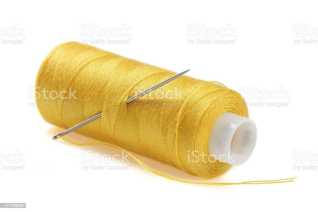 Yellow bobbin of thread with needle royalty-free stock photo