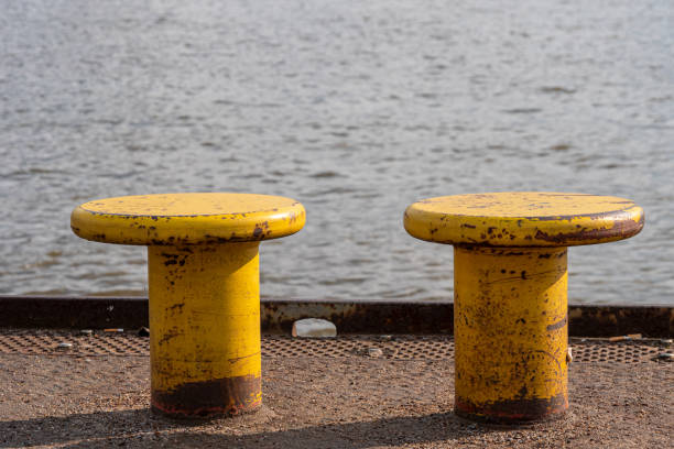 Yellow bollards on the harbor wall for attachment to the ship stock photo