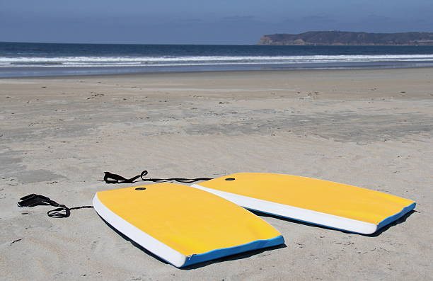 Yellow Boogie Boards in Sand on Beach Horizontal stock photo