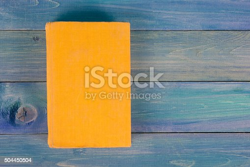 istock Yellow book on blue wooden background 504450504