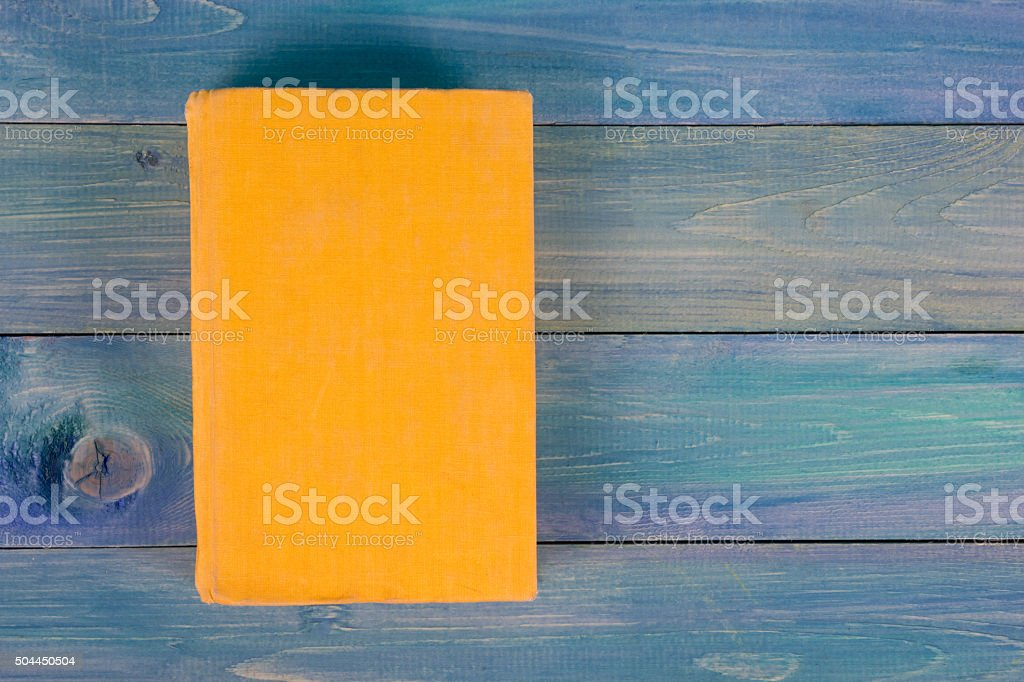 Yellow book on blue wooden background stock photo