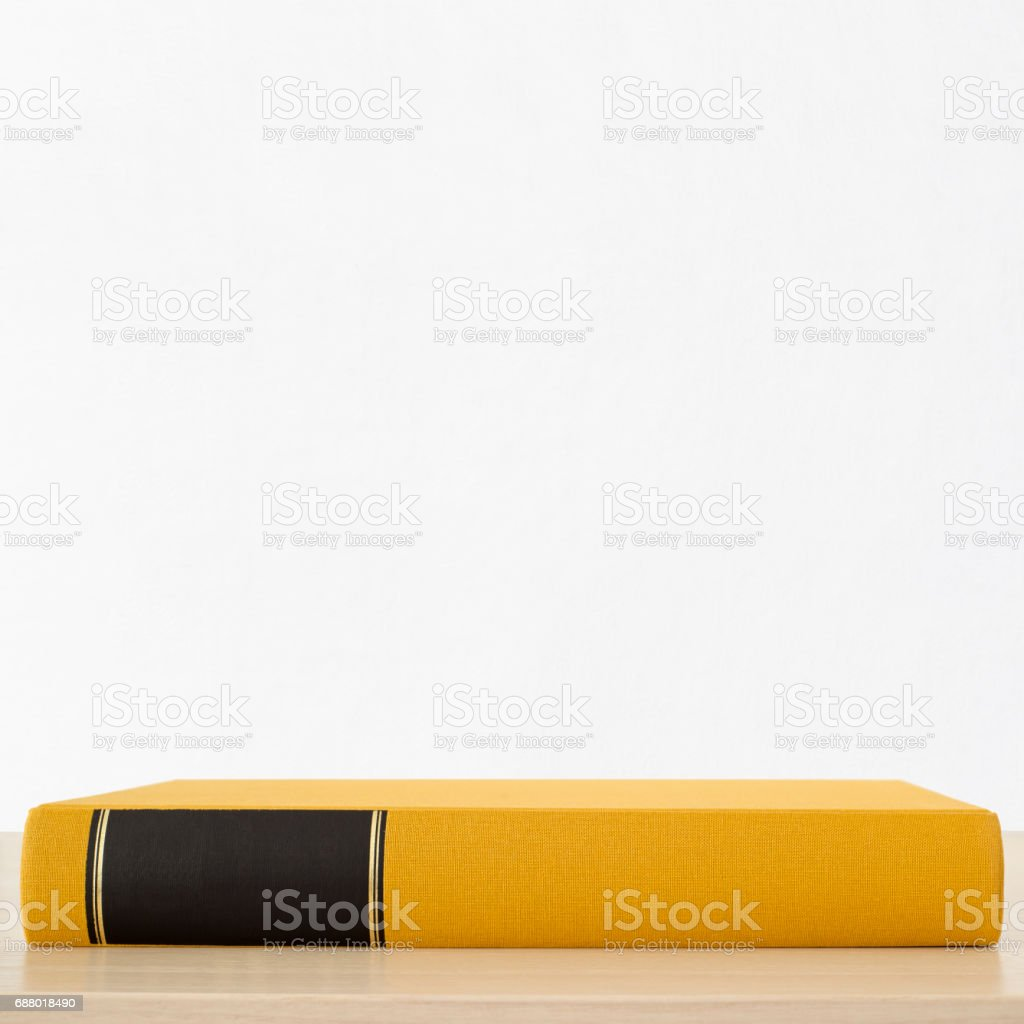 Yellow book with black frame on spine on the table stock photo