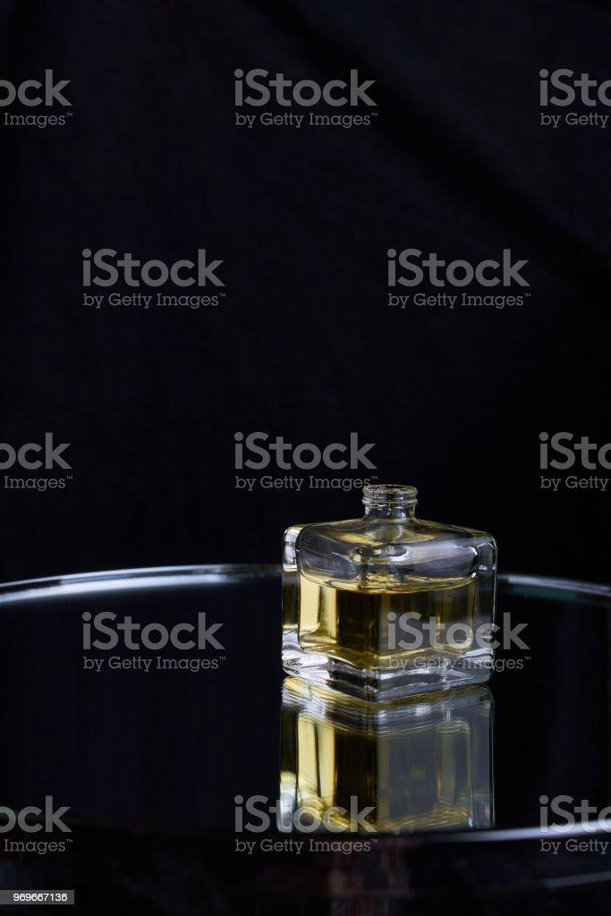 Yellow bottle of perfume spraying, isolated on black background stock photo