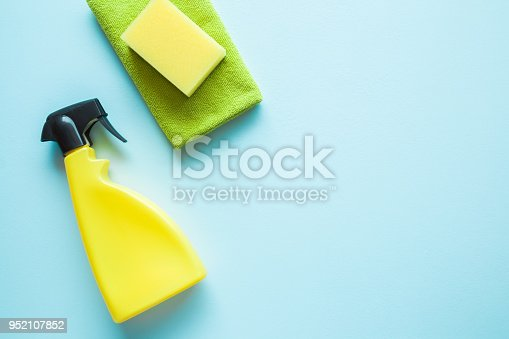 918825114 istock photo Yellow bottle, sponge and green microfiber rag for different surfaces cleaning in kitchen, bathroom or other rooms. Empty place for text or logo on blue background. Spring general or regular clean up. 952107852