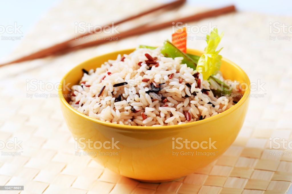 Yellow bowl of mixed rice with fresh greens on top  stock photo