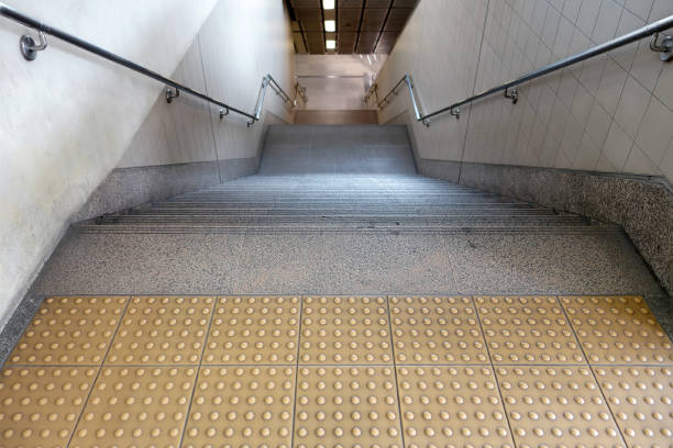 yellow braille block and dark granite stairs with stainless steel railings on concrete wall stock photo