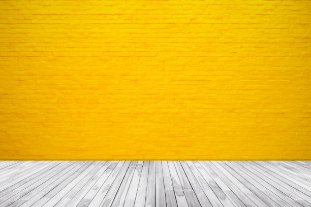 Yellow brick wall texture with wood floor background Yellow brick wall texture with wood floor background for pattern design. yellow stock pictures, royalty-free photos & images