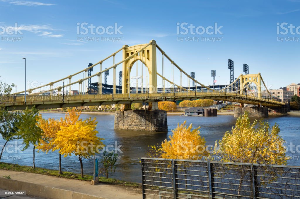 Yellow bridges and fall foliage of Pittsburgh, Pennsylvania. View of the Roberto Clemente Bridge over the Allegheny River in Pittsburgh, Pennsylvania, in autumn. Allegheny River Stock Photo