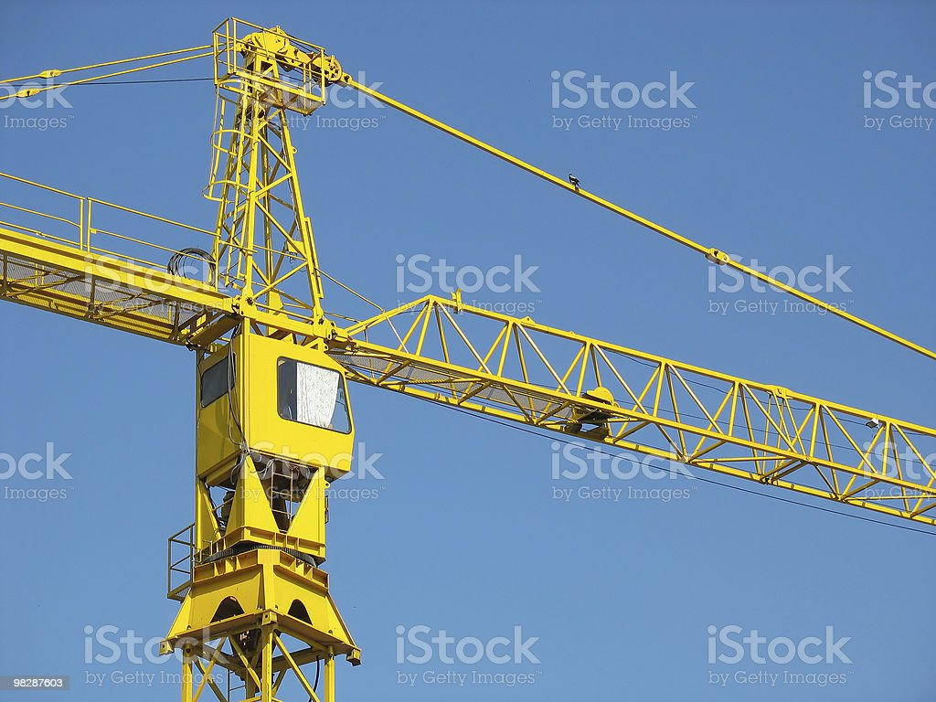 yellow building crane detail over blue sky background royalty-free stock photo