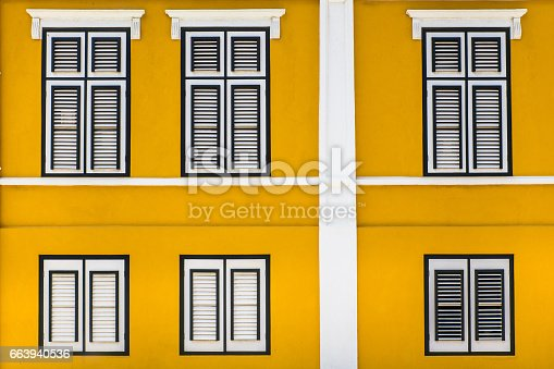 Vibrant yellow exterior building facade with windows