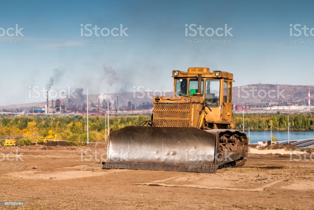 Yellow bulldozer against the backdrop of an industrial landscape stock photo