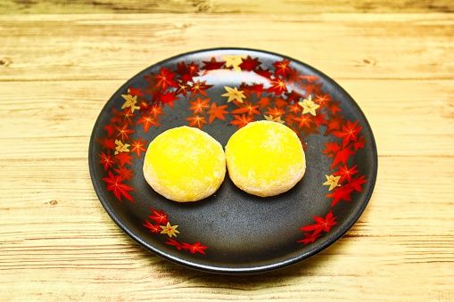 Yellow bun on a plate with autumn leaves, autumn image
