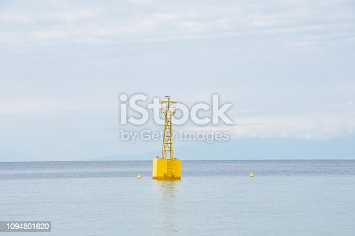 1030314738 istock photo Yellow buoy floating on a calm sea with sky in the background 1094801620