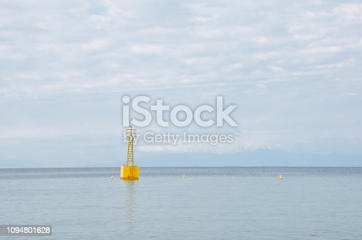 1030314738 istock photo Yellow buoy floating on a calm sea with sky in the background 1094801628