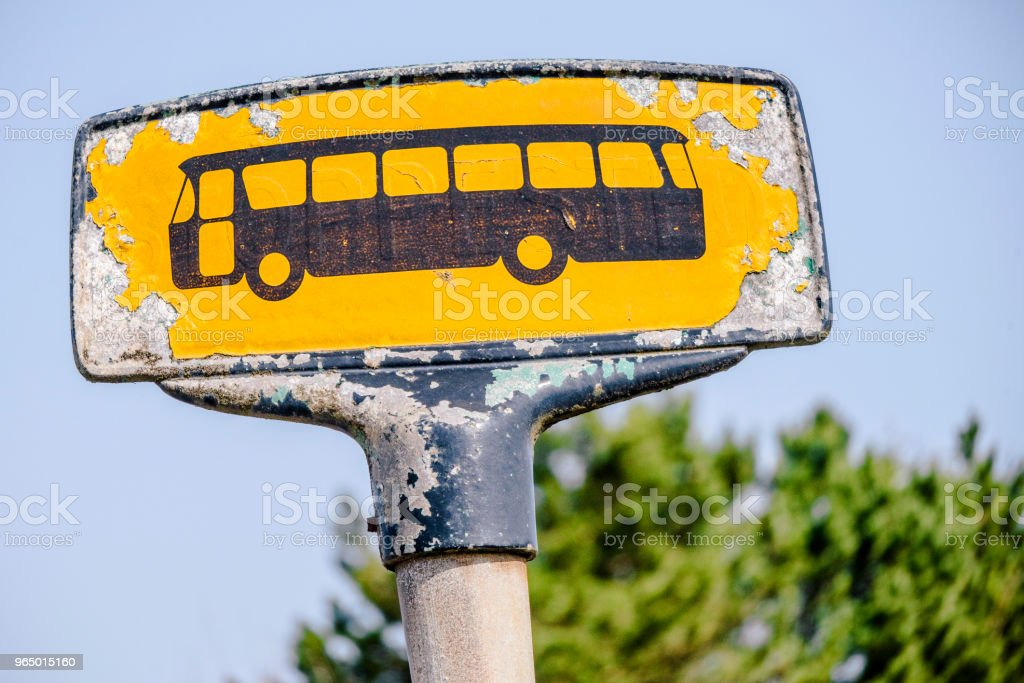 Yellow bus stop sign with a rough look stock photo