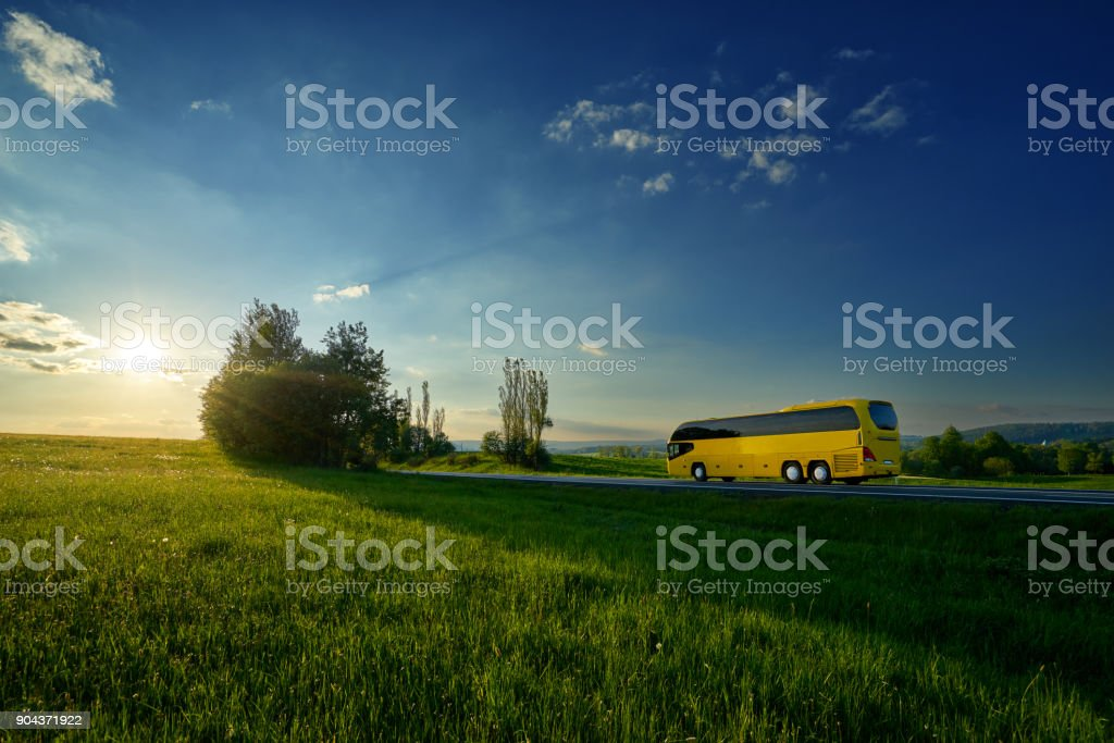 Yellow bus traveling on the road between green meadows in a rural landscape at sunset stock photo