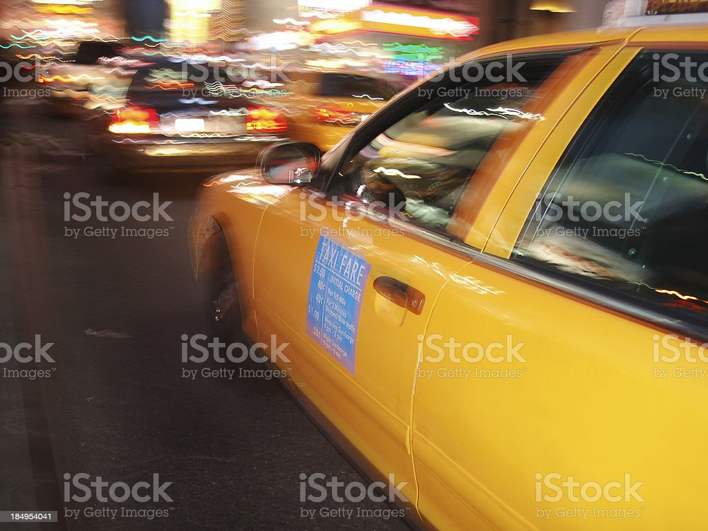 Yellow cab at night, moving in traffic royalty-free stock photo