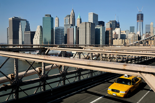 Yellow cab on a bridge, with skyscapers in background - New York City in USA. February 12, 2012