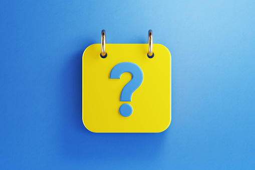 Yellow calendar with blue question mark on blue background. Horizontal composition with copy space. Top view.