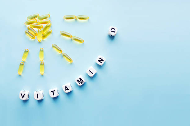 yellow capsules in the form of the sun with rays and the word vitamin d from white cubes - vitamin d стоковые фото и изображения