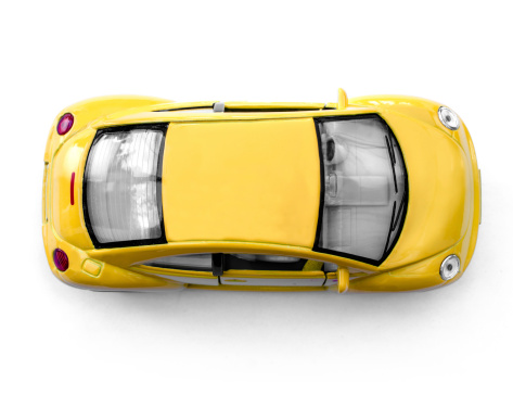London, England, January 26, 2014: A yellow Volkswagen Beetle toy car seen from above. This photo was taken in a studio in front of a white background