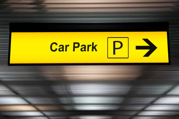 yellow car park sign with arrow pointing to car parking zone at airport terminal stock photo