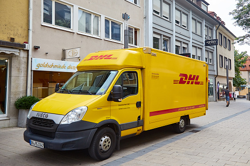 Heilbronn, Germany - August 9, 2019: A yellow car with the DHL logo is parked on the street. DHL is an international company for the fast delivery of documents and goods. Blur