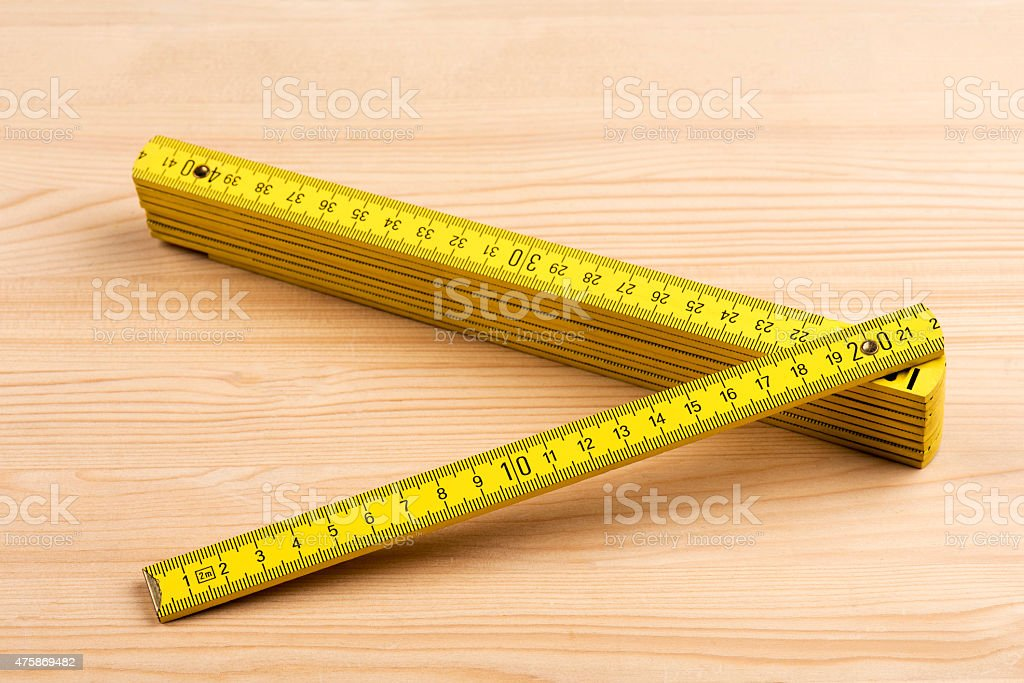 Yellow carpenter rule on wooden background stock photo