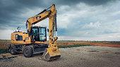 istock Yellow CAT industrial excavator with stormy sky. 1259112822