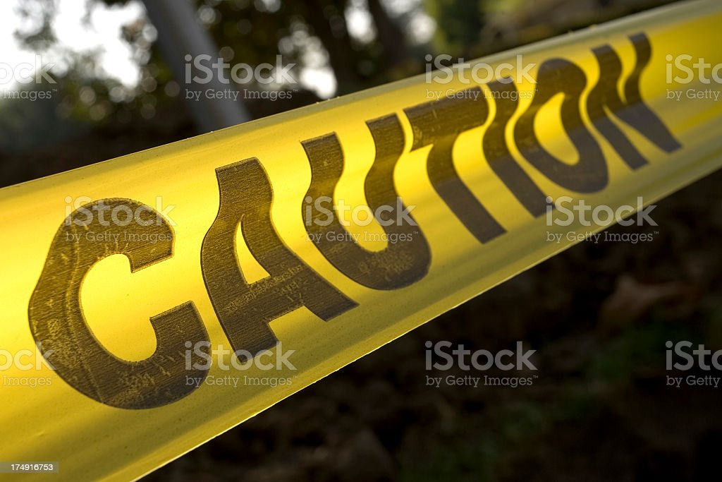 Yellow caution tape stretched across an exterior background royalty-free stock photo