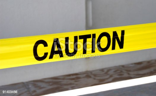 istock Yellow caution tape with a blurry background 91403456