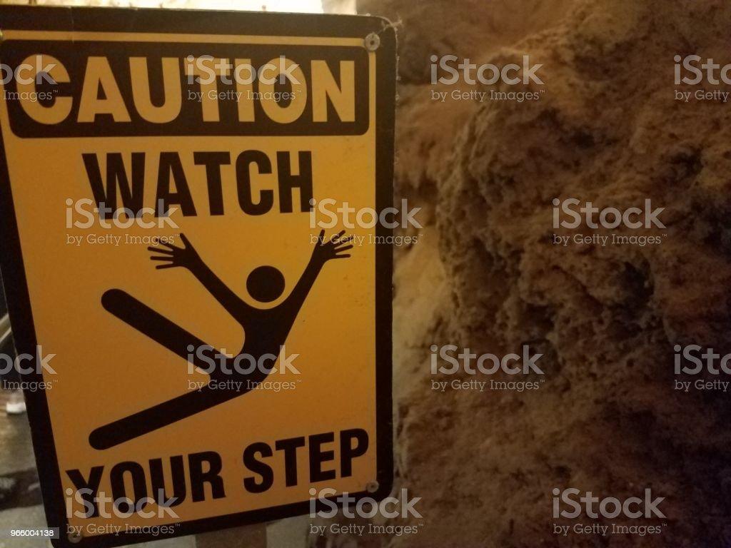 gul varning titta på dina steg logga i grotta - Royaltyfri Extrema Sporter Bildbanksbilder