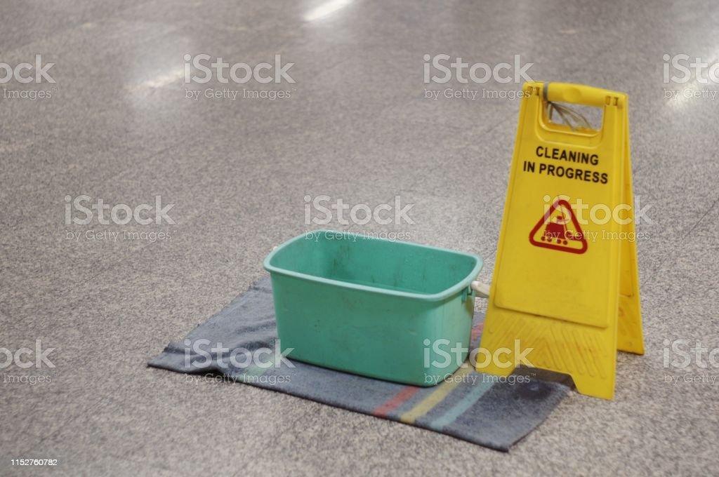 Yellow Caution wet floor cleaning in progress sign on wet floor with...